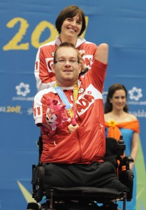 November 16 2011 - Guadalajara, Mexico: Josh Vandervies waves to his Canadian fans with his assistant Dalia Mykolaiteine behind him after receiving his Bronze Medal in Boccia BC4 in the Multipurpose Gymnasium Revolución at the 2011 Parapan American Games in Guadalajara, Mexico. Photo: Matthew Murnaghan/Canadian Paralympic Committee